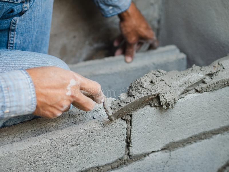 Professional construction worker laying bricks with cement royalty free stock photos