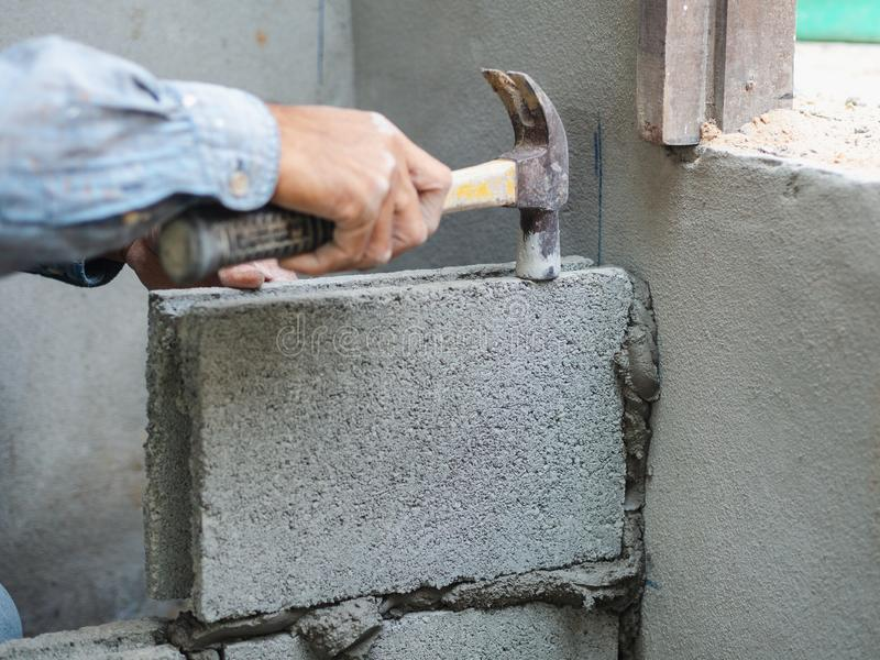 Professional construction worker laying bricks with cement stock images