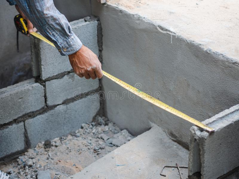 Professional construction worker uses measuring Tape for measure and laying bricks with cement royalty free stock images