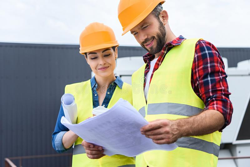 professional constructors in hardhats working with blueprints royalty free stock images