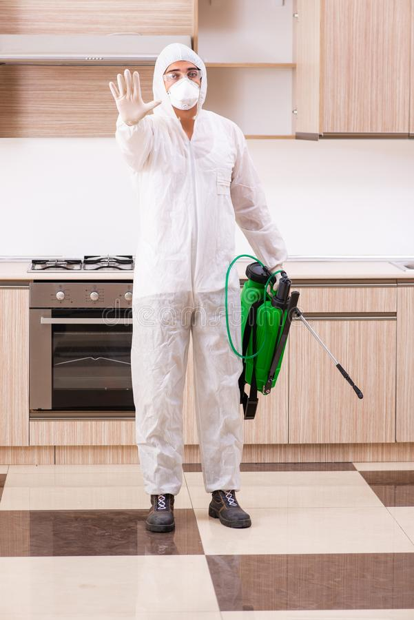 The professional contractor doing pest control at kitchen. Professional contractor doing pest control at kitchen stock photography