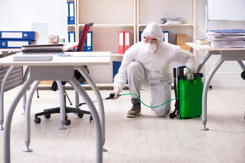 The professional contractor doing pest control at office. Professional contractor doing pest control at office royalty free stock images