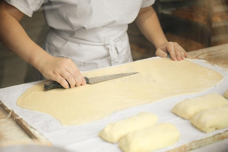 Professional cook cuts dough for baking in a small bakery stock photos