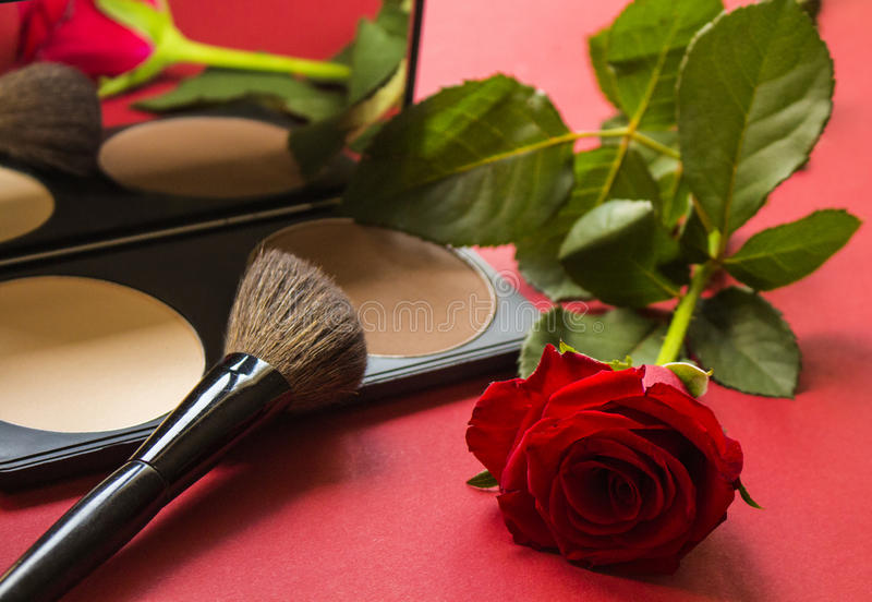 Professional cosmetics correcting powder, brush and rose on red textured surface. stock image