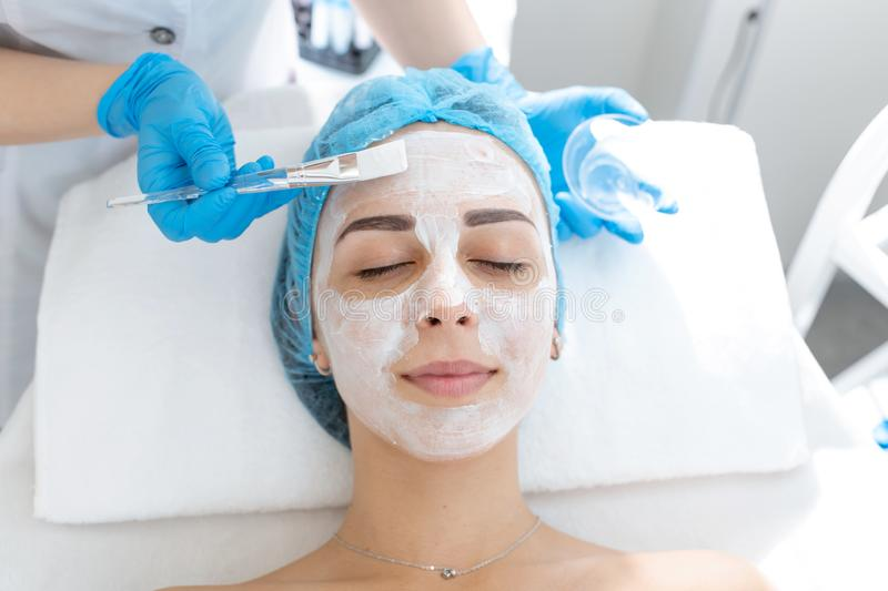 A professional cosmetologist applies a nourishing cream on the patient`s face. Moisturizing, cleaning and facial skin care. Cosmetic procedures stock photography