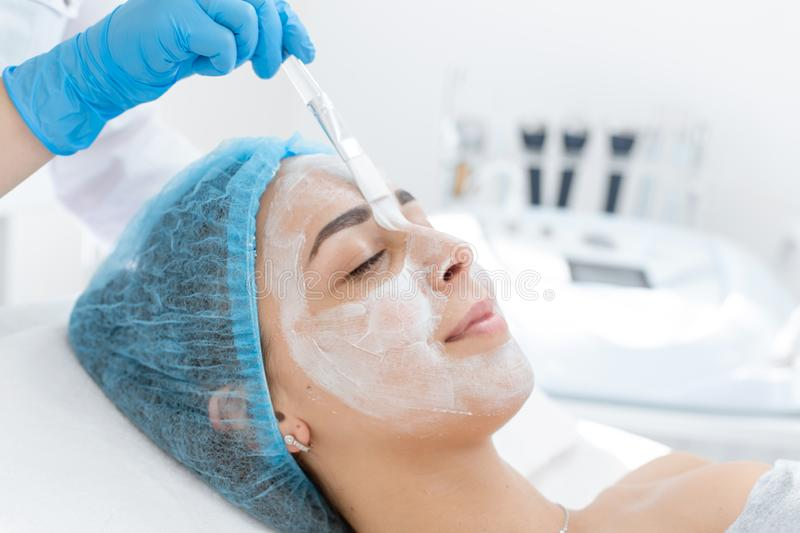 A professional cosmetologist applies a nourishing cream on the patient`s face. Moisturizing, cleaning and facial skin care. Cosmetic procedures royalty free stock photo