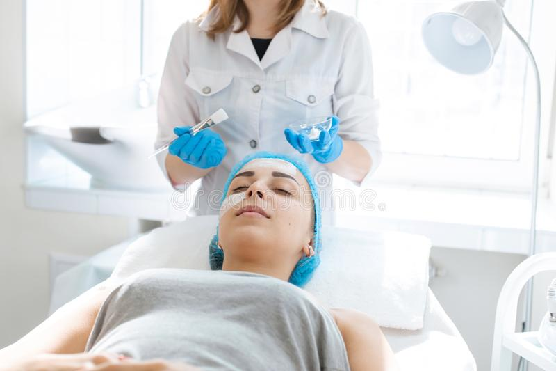 A professional cosmetologist applies a nourishing cream on the patient`s face. Moisturizing, cleaning and facial skin care. Cosmetic procedures stock image