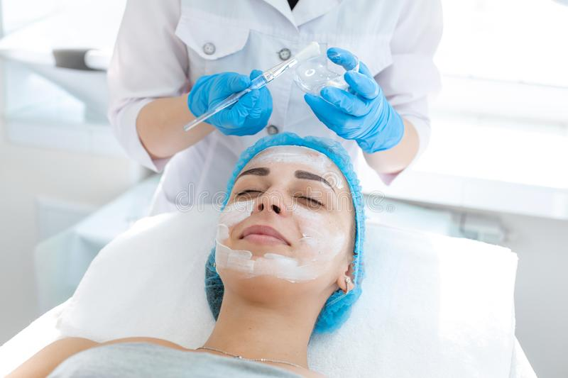 A professional cosmetologist applies a nourishing cream on the patient`s face. Moisturizing, cleaning and facial skin care. Cosmetic procedures royalty free stock images