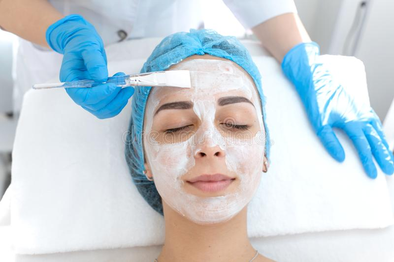 A professional cosmetologist applies a nourishing cream on the patient`s face. Moisturizing, cleaning and facial skin care. Cosmetic procedures stock images