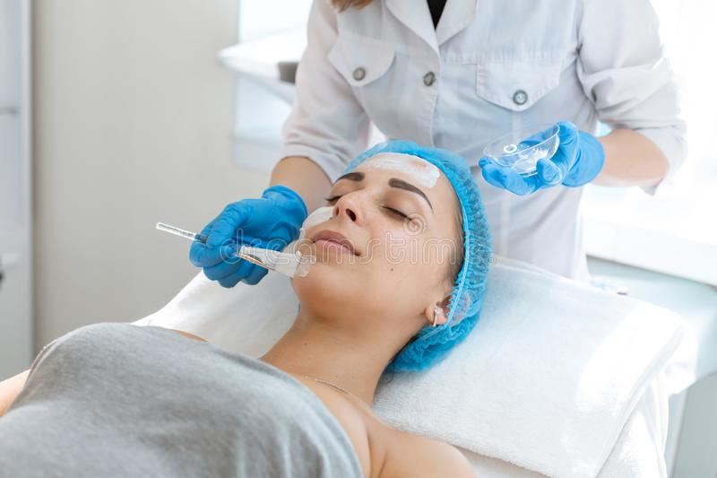 A professional cosmetologist applies a nourishing cream on the patient`s face. Moisturizing, cleaning and facial skin care. Cosmetic procedures stock photos