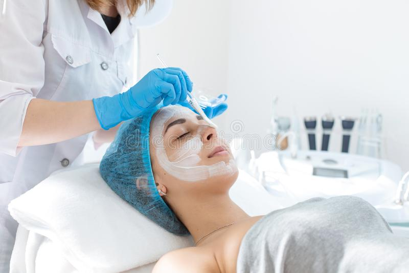A professional cosmetologist applies a nourishing cream on the patient`s face. Moisturizing, cleaning and facial skin care. Cosmetic procedures royalty free stock image