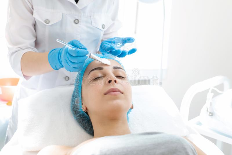 A professional cosmetologist applies a nourishing cream on the patient`s face. Moisturizing, cleaning and facial skin care. Cosmetic procedures royalty free stock photography