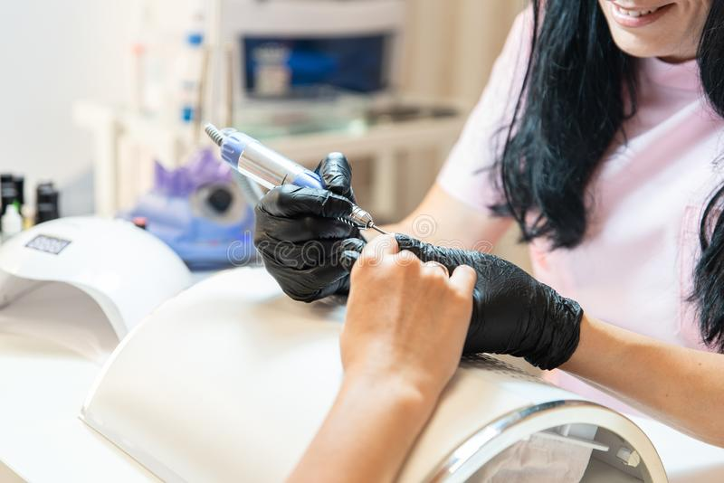 Professional cosmetologist makes manicure for woman using electric nail file. Process close up. Woman in beauty salon. Beauty and royalty free stock photos