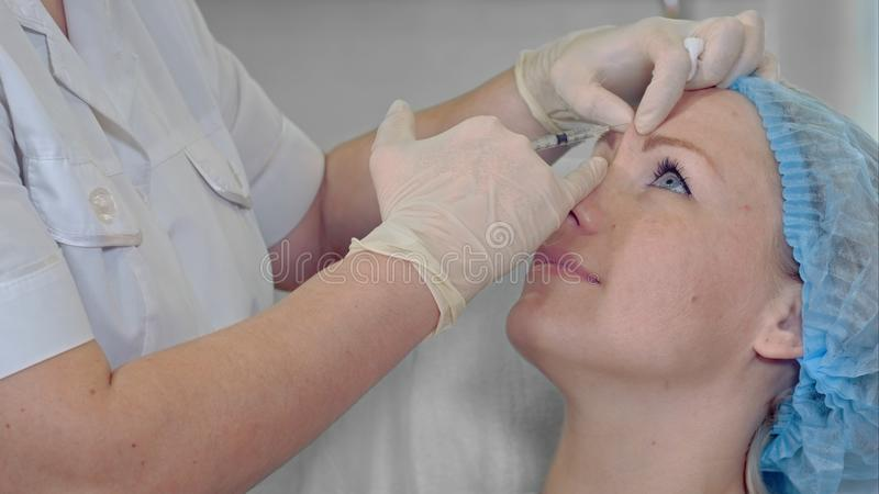 Professional cosmetologist making beauty injections to her female client revitalization anti aging botox beauty fillers. Hyaluronic professional concept. Close royalty free stock photos