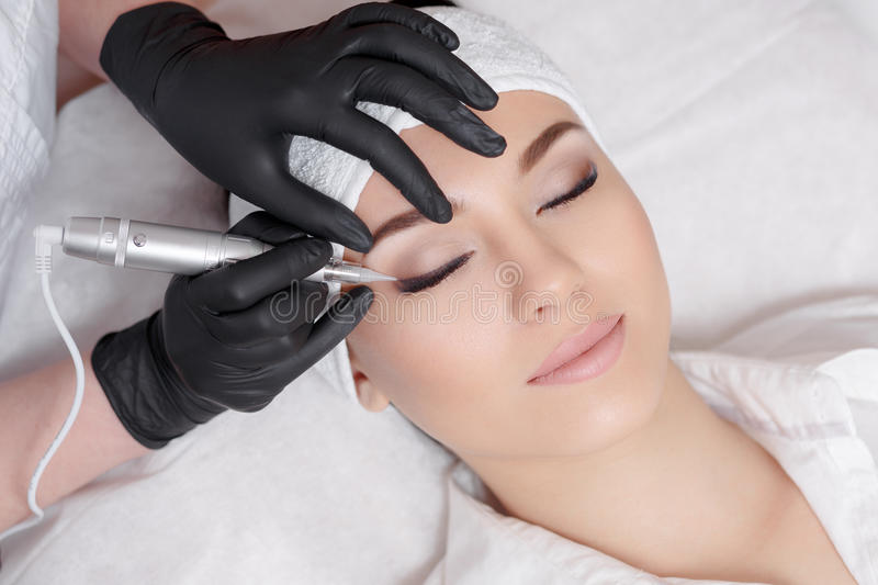 Professional cosmetologist wearing black gloves making permanent makeup royalty free stock images