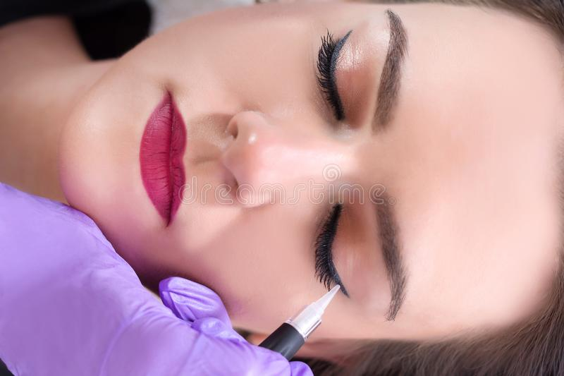 Professional cosmetologist wearing purple gloves making permanent eyeliner royalty free stock photo