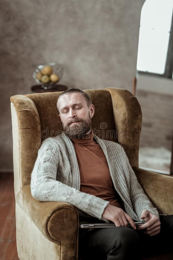 Professional counselor wearing grey cardigan having nap in armchair. Nap in armchair. Professional counselor wearing grey cardigan having nap in armchair while stock photos