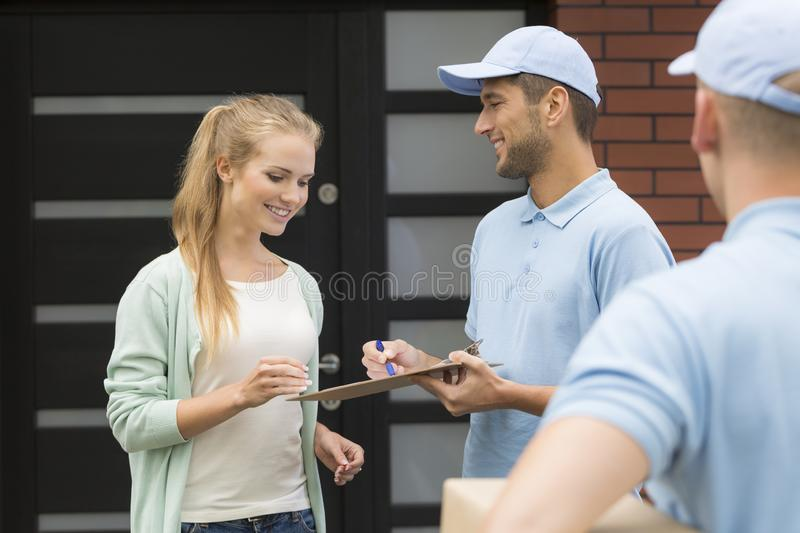 Professional couriers delivering package to smiling woman. Professional couriers delivering package to smiling women signing receipt stock photos