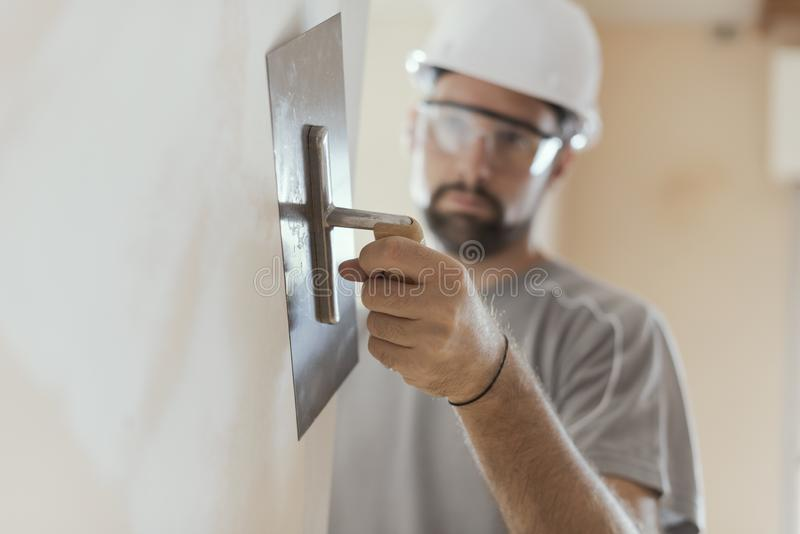 Professional craftsman applying plaster with a trowel stock photography