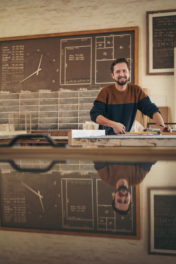 Professional craftsman smiling while at work in his studio stock images
