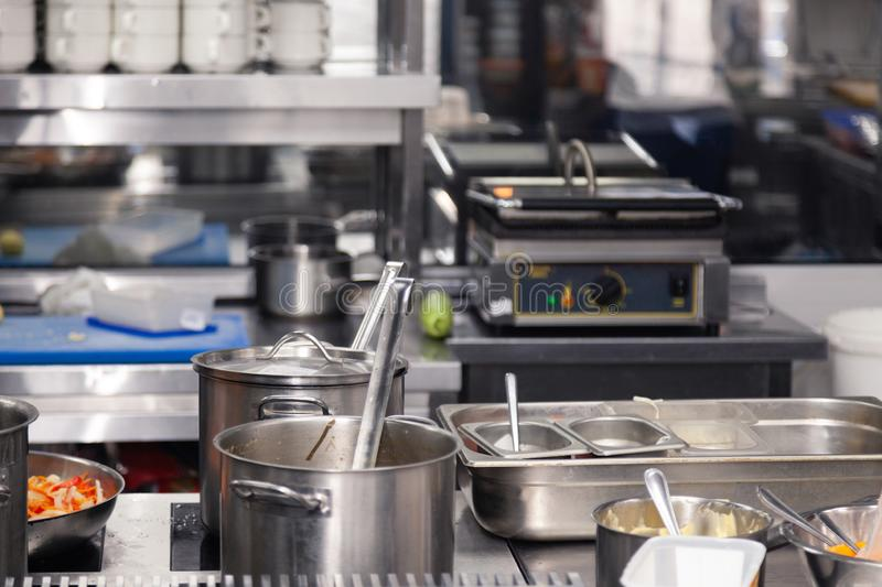 Professional cuisine restaurant. Kitchen utensils, plate with metal pots with lids and scoops. Ð¡oncept violation conditions and. Professional cuisine stock photos