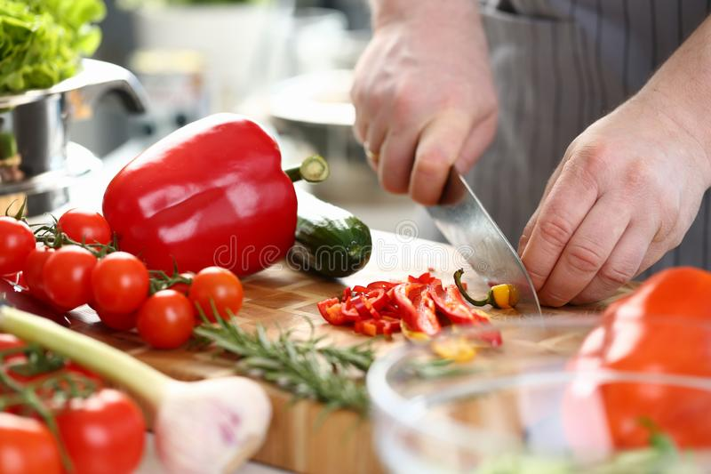 Professional Culinary Man Cutting Hot Chili Pepper. Man Chopping Yellow Ingredient to Small Pieces on Wooden Board for Tasty Salad. Healthy Dieting Recipe stock image