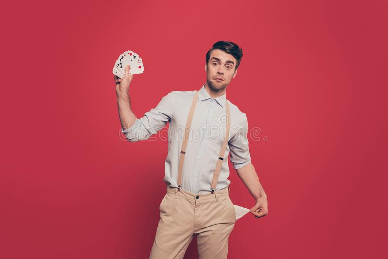 Professional, cunning magician, illusionist, gambler in casual outfit, holding, showing set of cards and empty pocket out, standin stock images