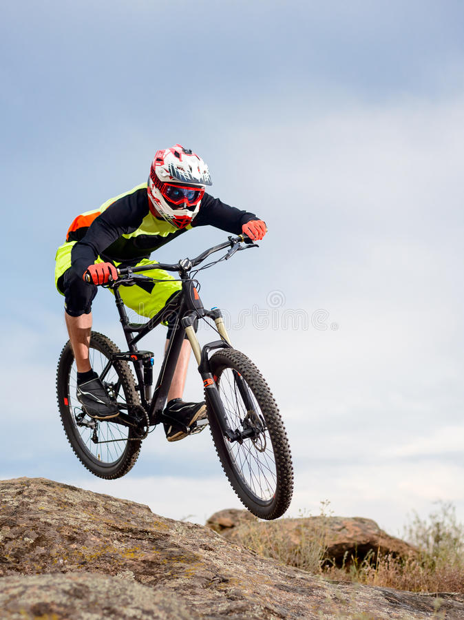 Professional Cyclist Riding the Bike Down Rocky Hill. Extreme Sport Concept. stock image
