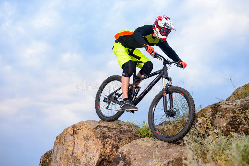 Professional Cyclist Riding the Bike on the Top of the Rock. Extreme Sport Concept. Space for Text. Professional Cyclist Riding the Bike on the Top of the Rock royalty free stock photography