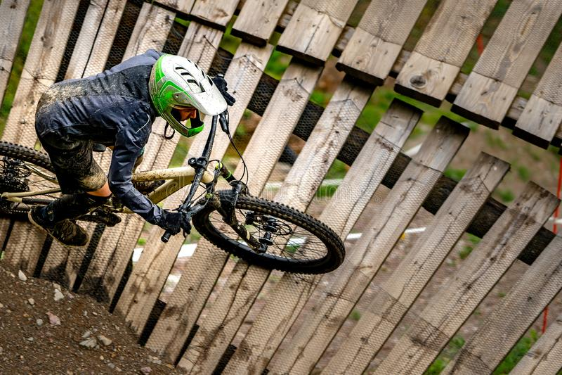 Professional Cyclist Riding the Mountain Bike on the wall. Extreme Sport and Enduro Biking Concept. stock photography