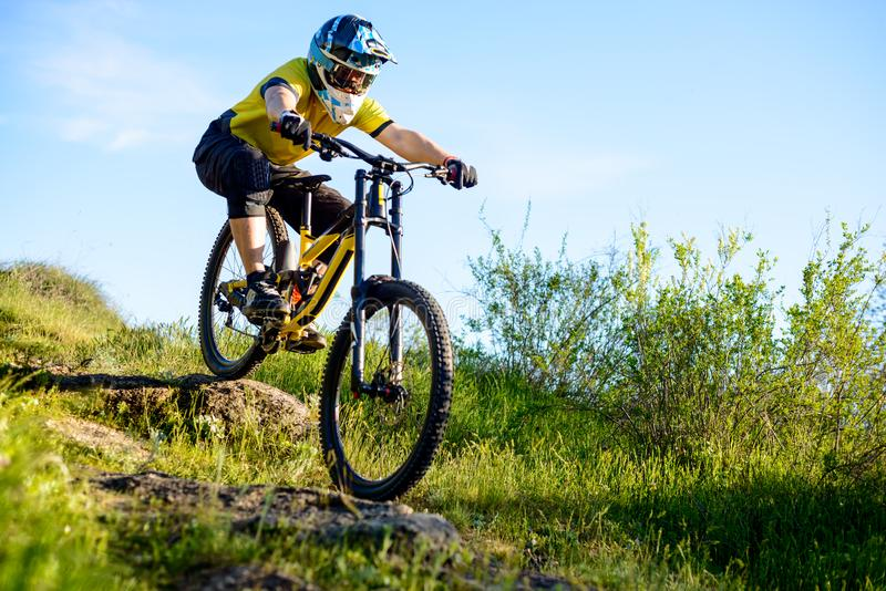 Professional Cyclist in Yellow T-shirt and Helmet Riding Bike Down Rocky Hill. Extreme Sport Concept. royalty free stock photo