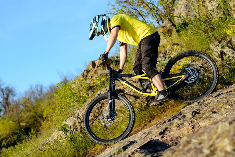 Professional Cyclist in Yellow T-shirt and Helmet Riding Mountain Bike Down Rocky Hill. Extreme Sport Concept. stock photo