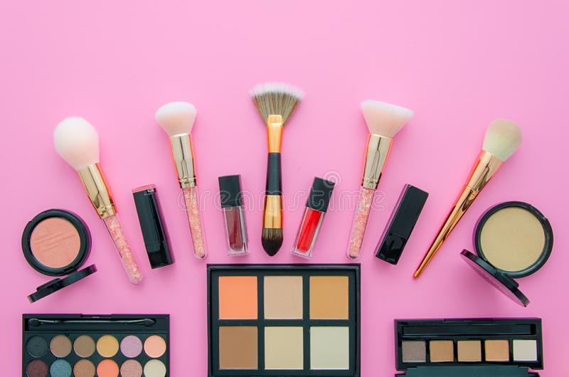 Professional decorative cosmetics, makeup tools on pink background. Flat composition beauty, fashion. top view stock image