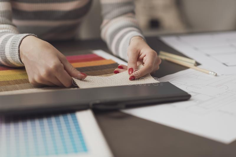 Professional decorator choosing fabric swatches stock images
