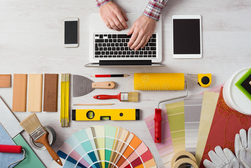 Professional decorator working at desk. Professional decorator's hands working at his desk and typing on a laptop, color swatches, paint rollers and tools on royalty free stock photos