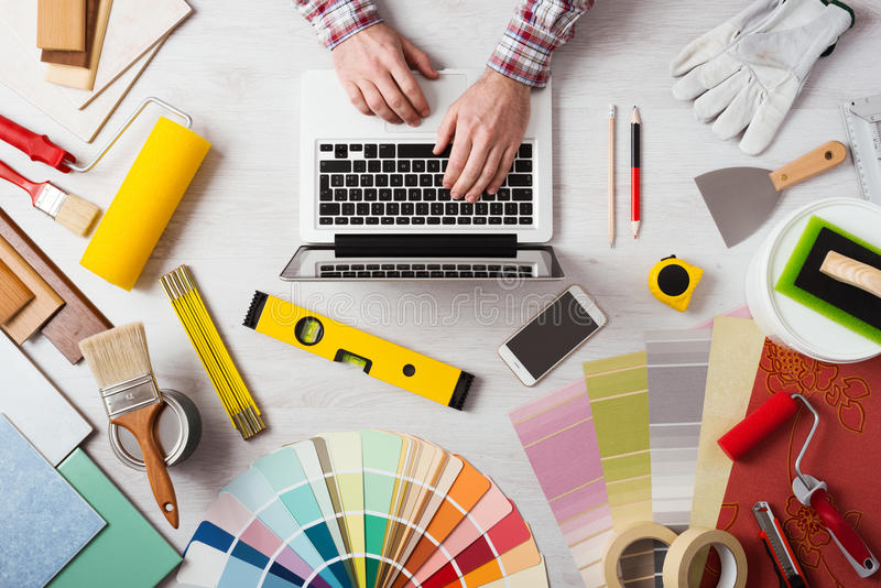 Professional decorator working at desk. Professional decorator's hands working at his desk and typing on a laptop, color swatches, paint rollers and tools on stock images