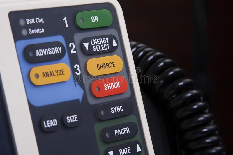 Professional defibrillator buttons close up, red shock button in main focus. Operating a medical AED device in a simple way stock photography