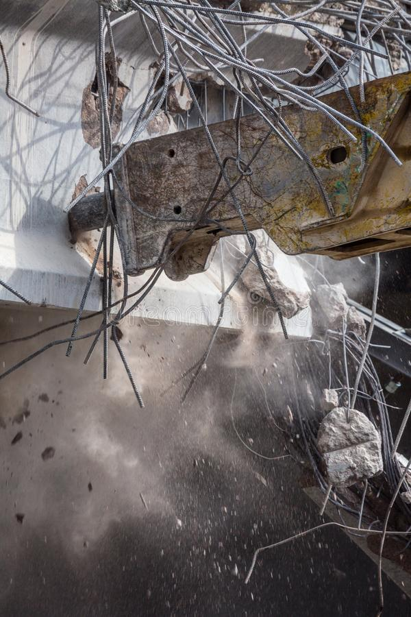 Professional demolition of reinforced concrete structures using industrial hydraulic hammer. Rods of metal fittings. Wreckage and royalty free stock photography