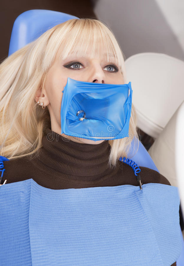 Professional dental equipment. The blonde woman in the dental chair with cofferdam on her mouth stock images