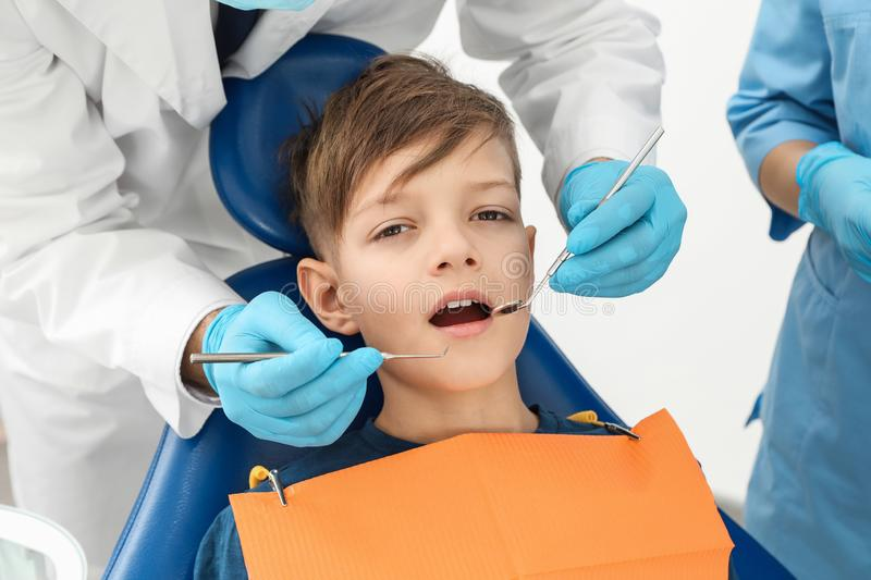 Professional dentist and assistant working with little boy. In clinic stock images