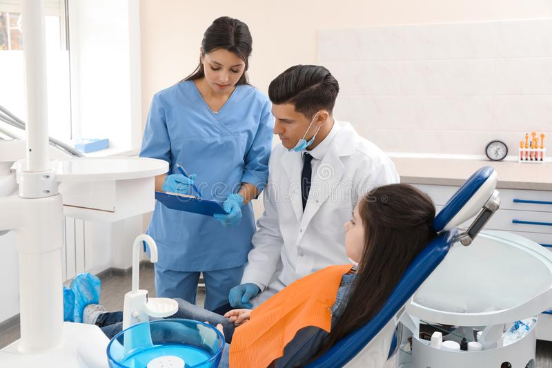 Professional dentist and assistant working with little girl royalty free stock image