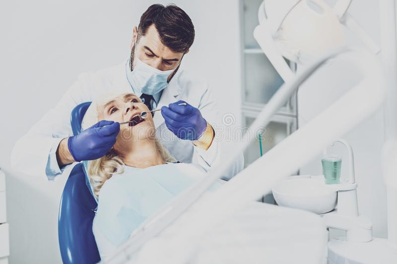 Professional dentist checking quality of teeth. Yearly checkup. Serious male person bowing head while examining his patient royalty free stock photo