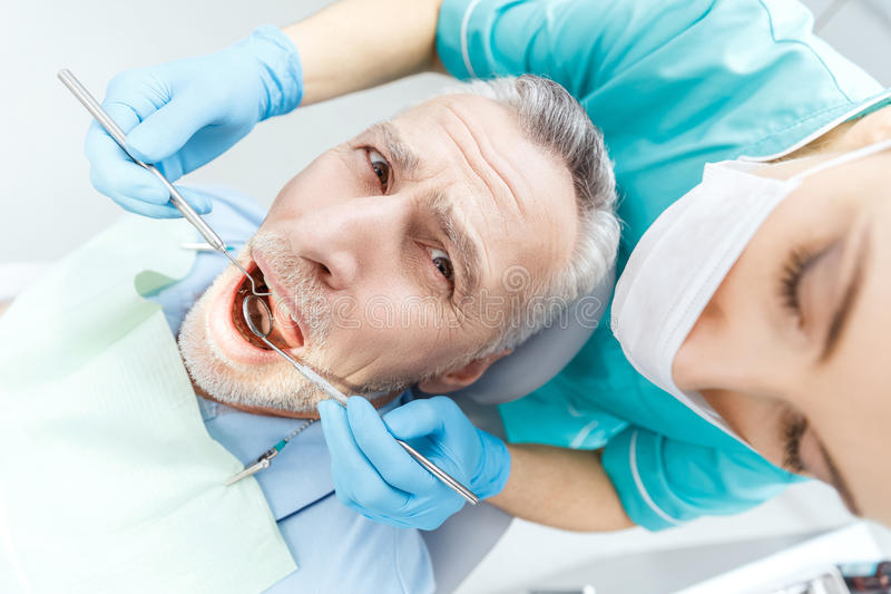 Download Professional Dentist Curing Scared Mature Patient In Dental Clinic Stock Image