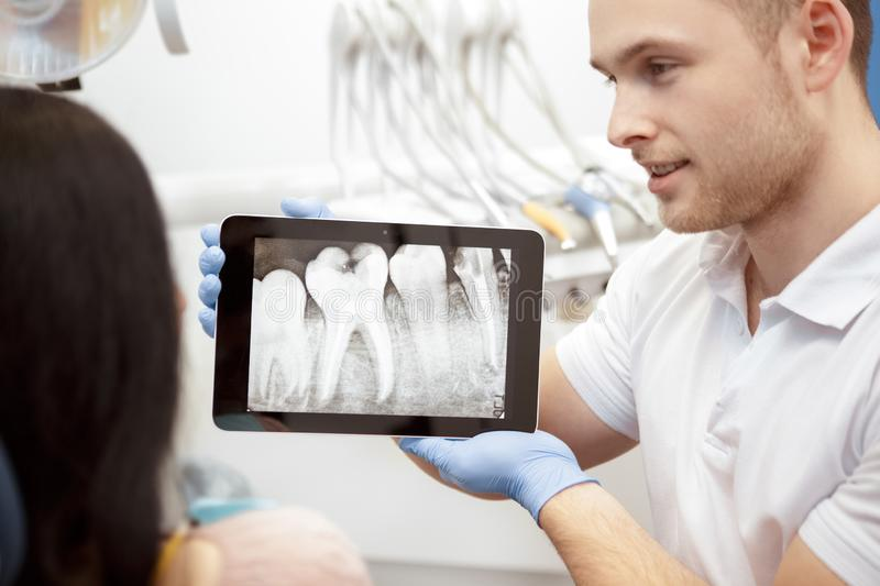 Professional dentist showing his client x-rays on a digital tablet stock images