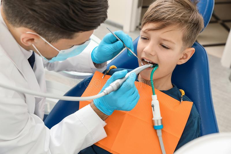 Professional dentist working with little boy. In clinic stock photography