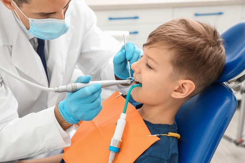 Professional dentist working with little boy. In clinic royalty free stock image