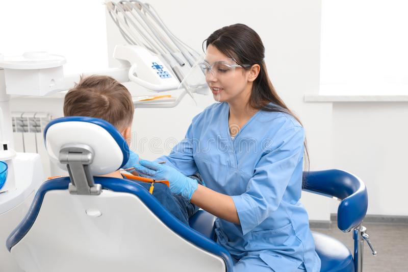 Professional dentist working with little boy royalty free stock photography