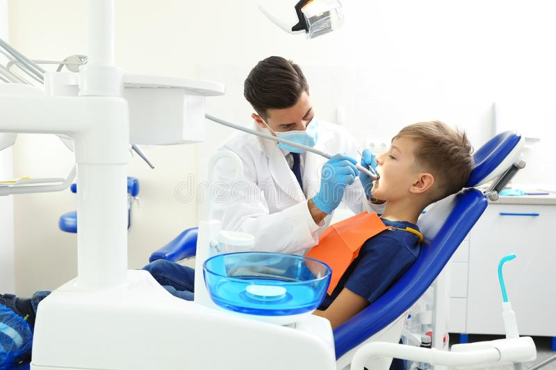 Professional dentist working with little boy. In clinic stock image