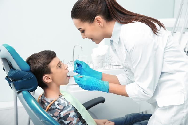 Professional dentist working with little patient in clinic stock images