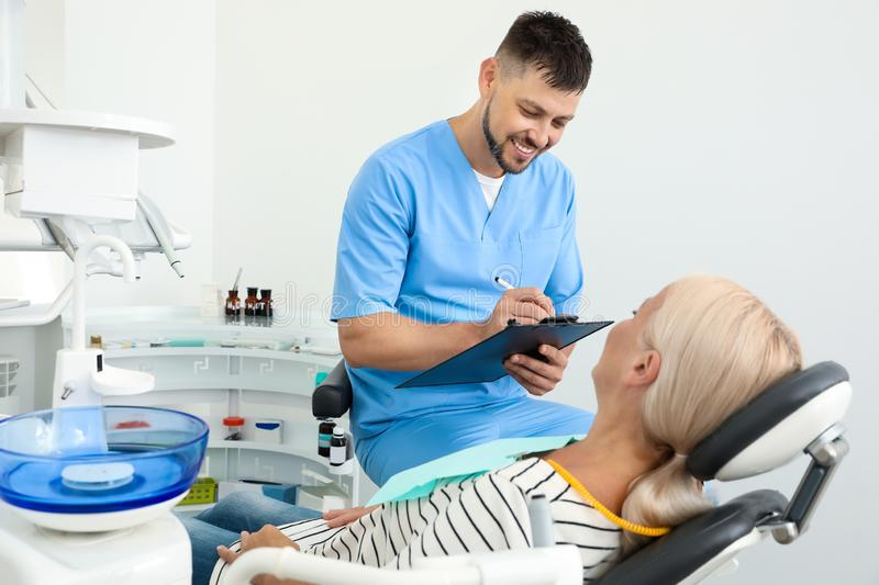 Professional dentist working with patient. In clinic royalty free stock photography